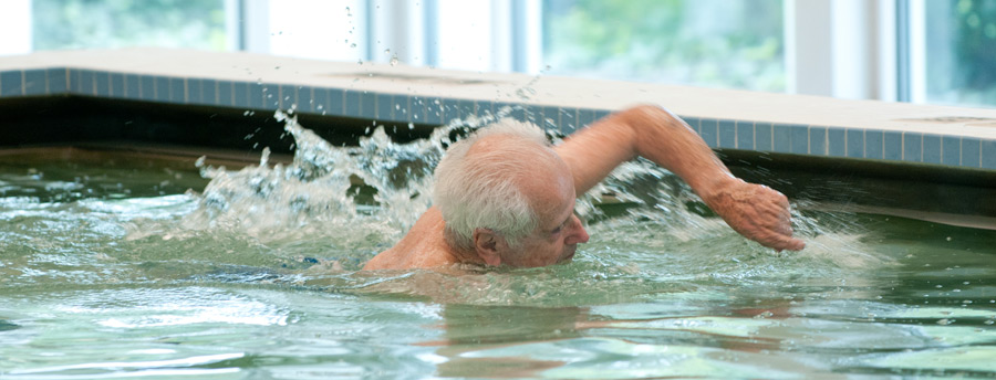 Active senior enjoying a swim in the pool at Acacia Village